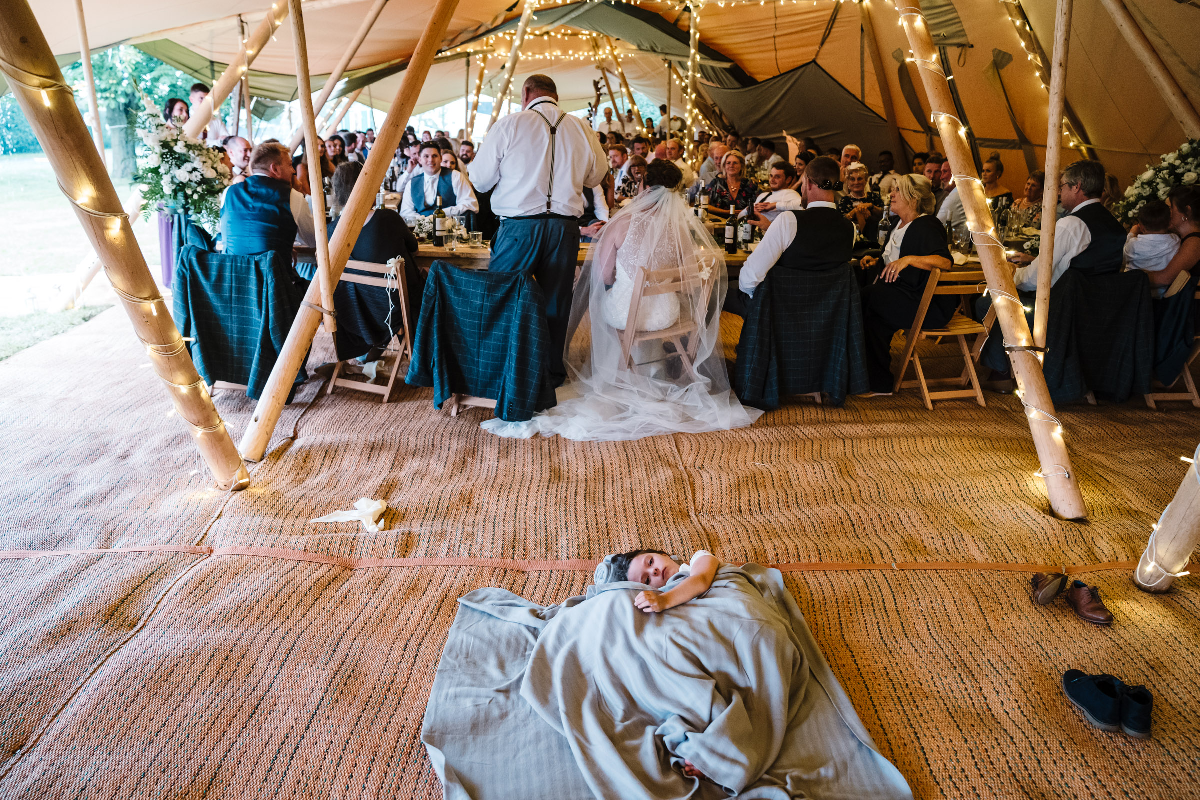 girls lying on the floor tucked up in a blanket during wedding breakfast