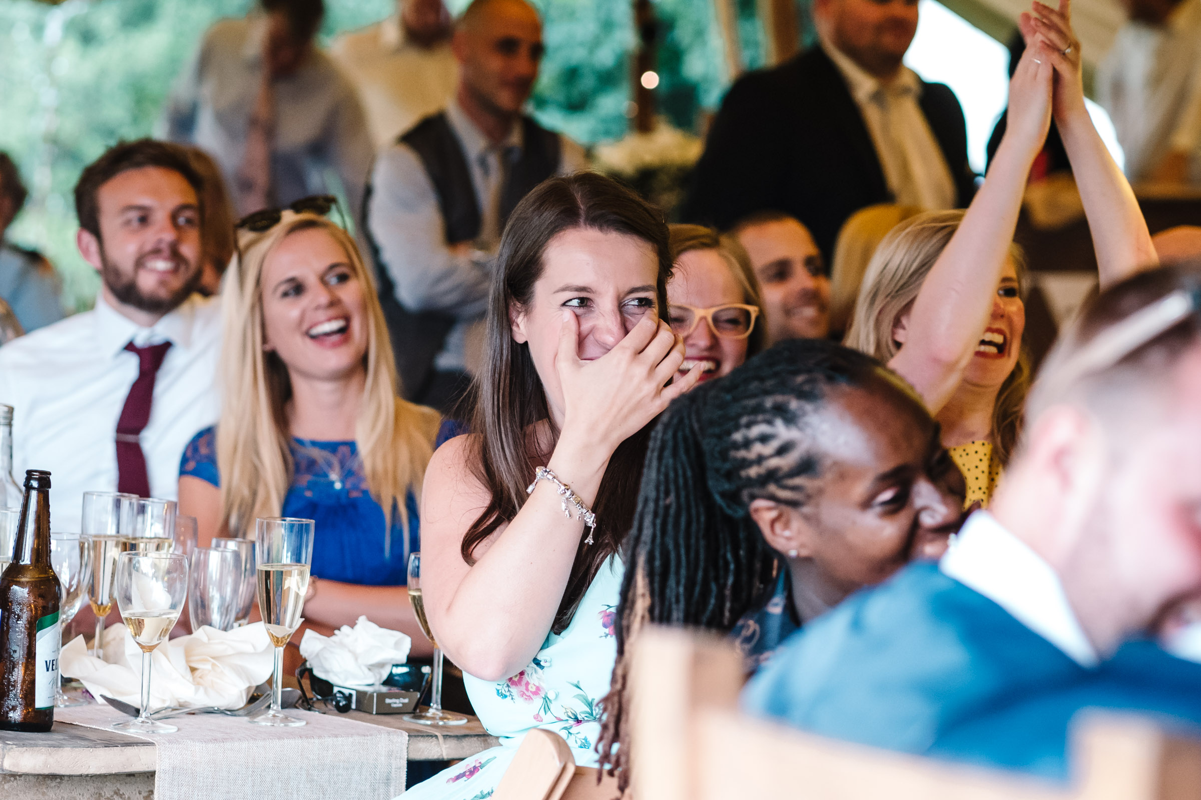 guests laughing during tipi wedding speeches