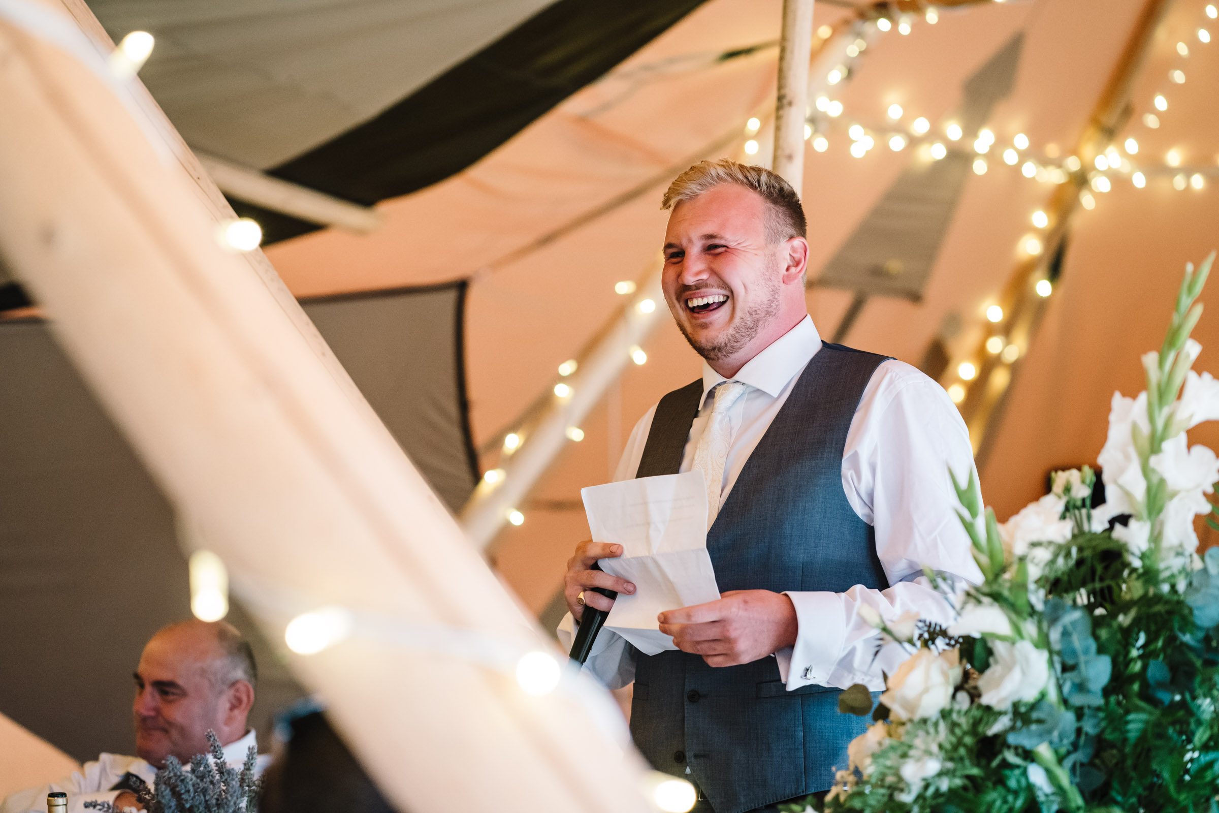 best man giving speech and laughing