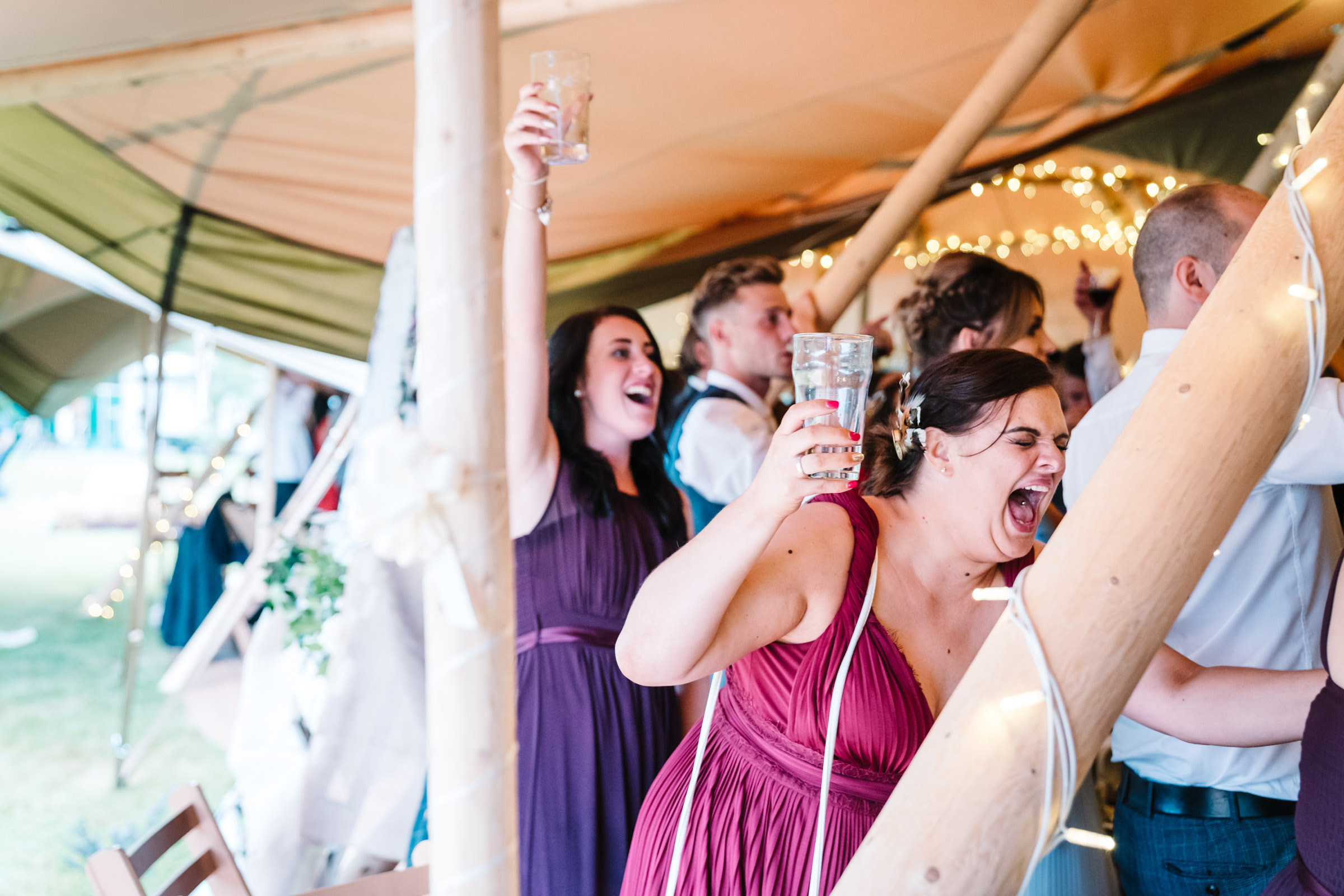 guests cheering after speeches at tipi wedding
