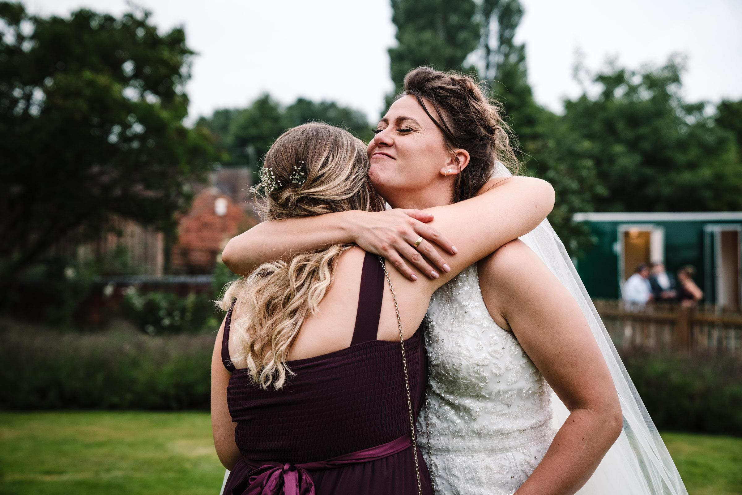 bride hugging bridesmaid at wedding