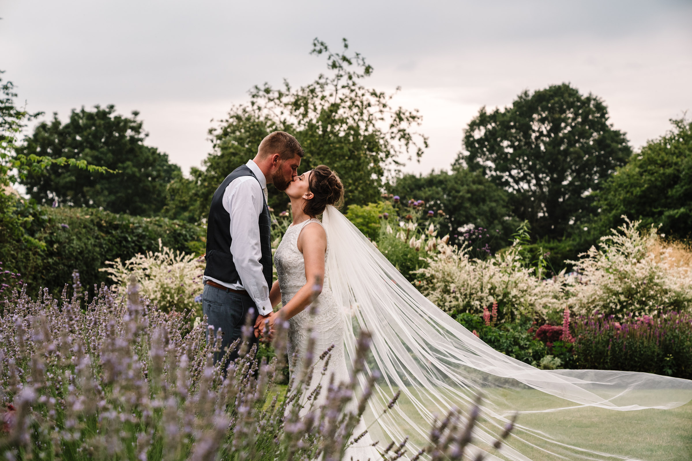 bride and groom kissing in gardens at tipi wedding