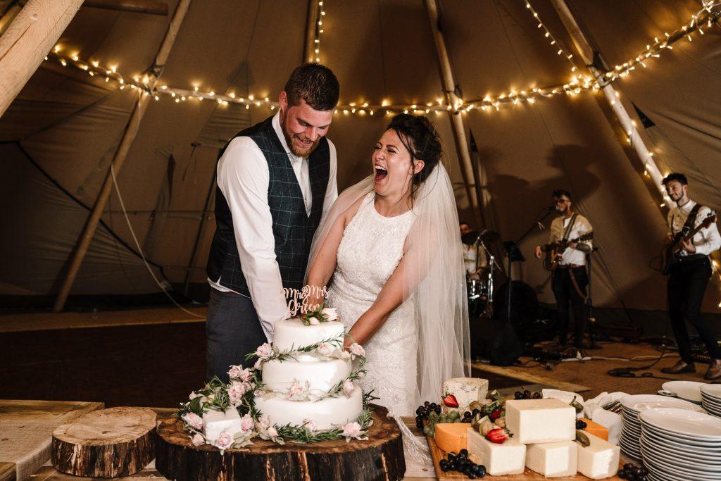Bride and groom cutting wedding cake, tipi wedding, warwickshire wedding photography