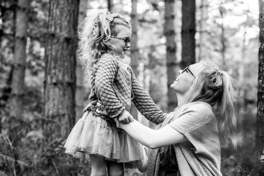 Mum and daughter looking at each other in the woods on photoshoot