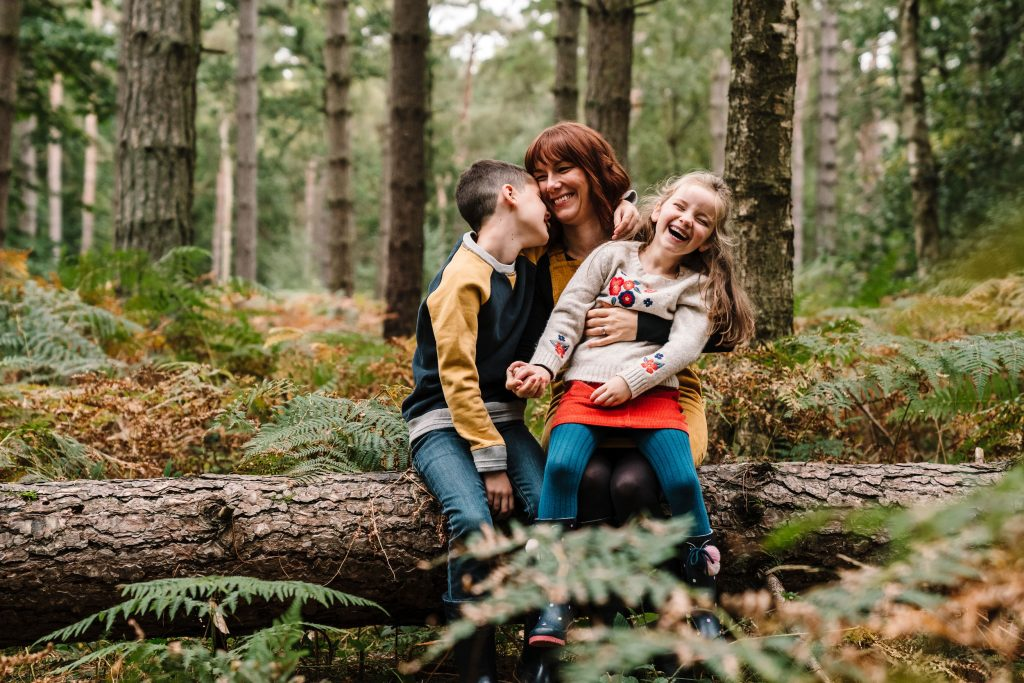 mum cuddling her 2 children, sitting on a log in the woods