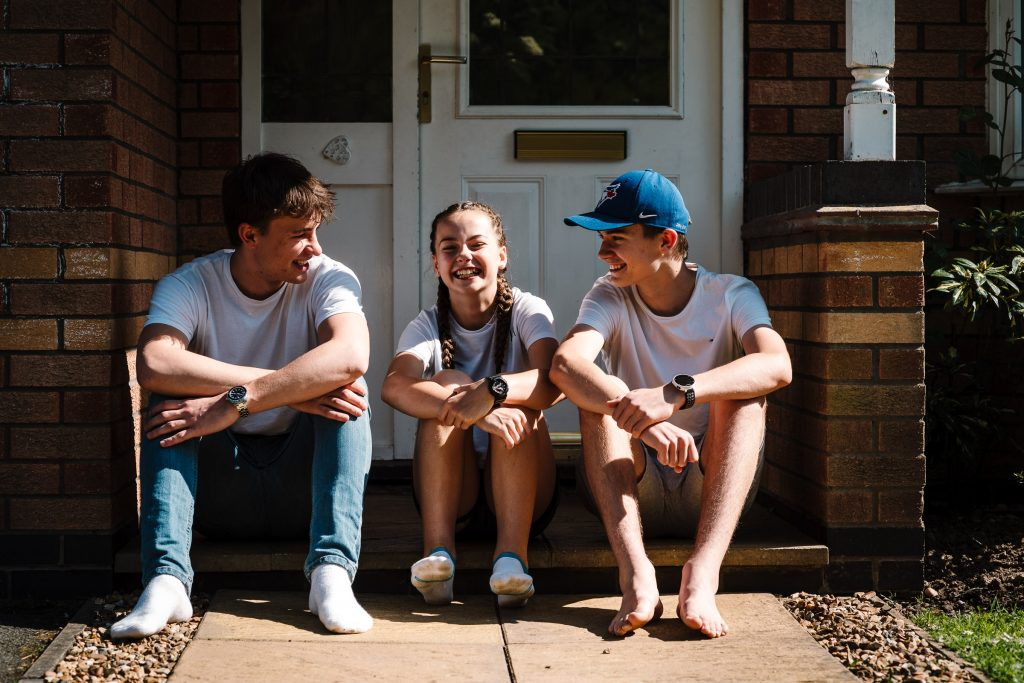 2 brothers and a sister sitting on doorstep. Family photography