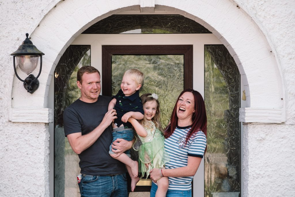 Doorstep photographs, family in front of their door laughing