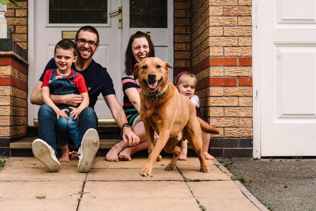 family sitting on doorstep laughing at dog