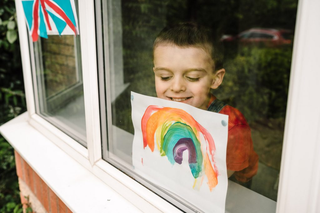 boy looking out of window during lockdown. Standing by painting of a rainbow