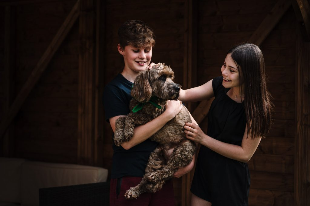 brother and sister cuddling dog in doorstep photograph session