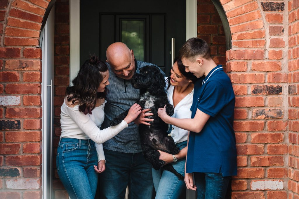 Family cuddling dog in doorstep photo shoot