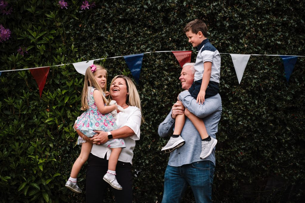 Family laughing in front garden- doorstep photo shoot