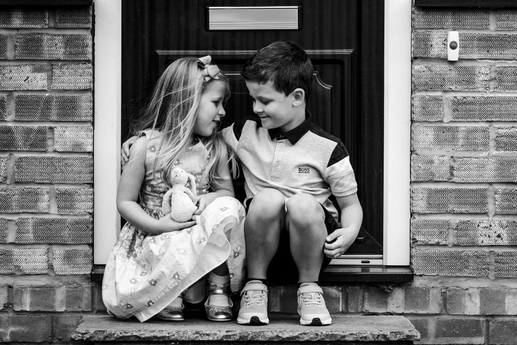 brother and sister sitting on front step in doorstep photo session
