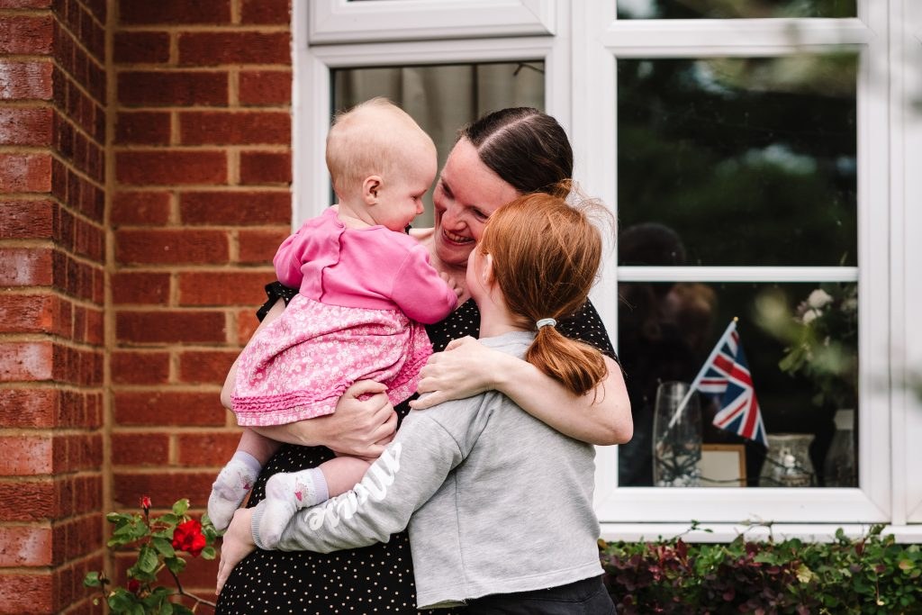 Mum cuddling daughters in doorstep photo shoot