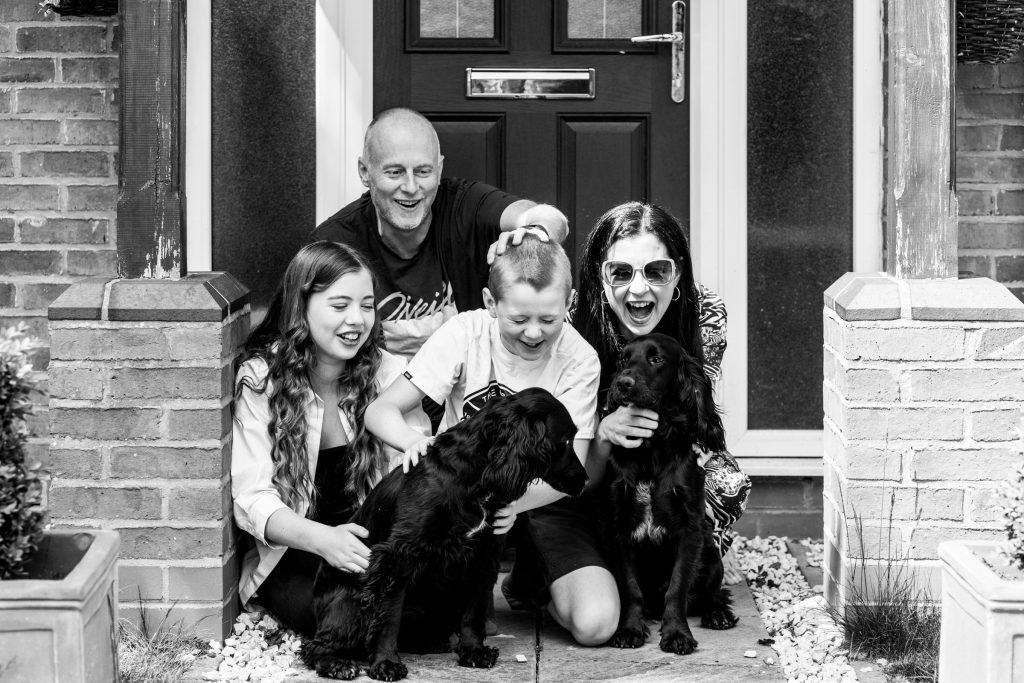 family laughing on doorstep photo shoot
