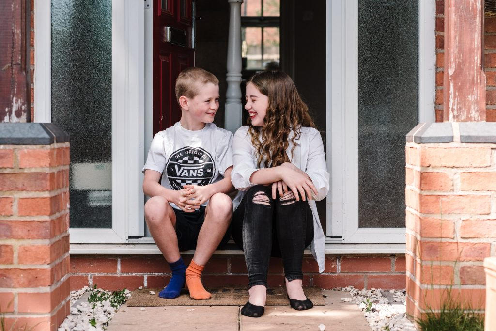 brother and sister laughing, sitting on doorstep for doorstep portrait