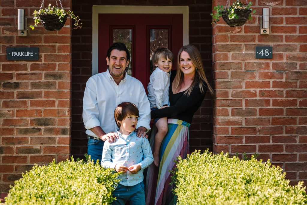 Family laughing in front of their front door, family doorstep photo shoot