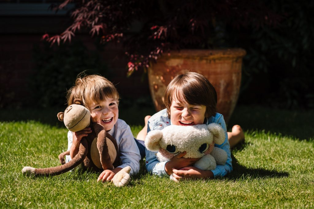 brothers laughing with their teddies on front garden, doorstep photo shoot