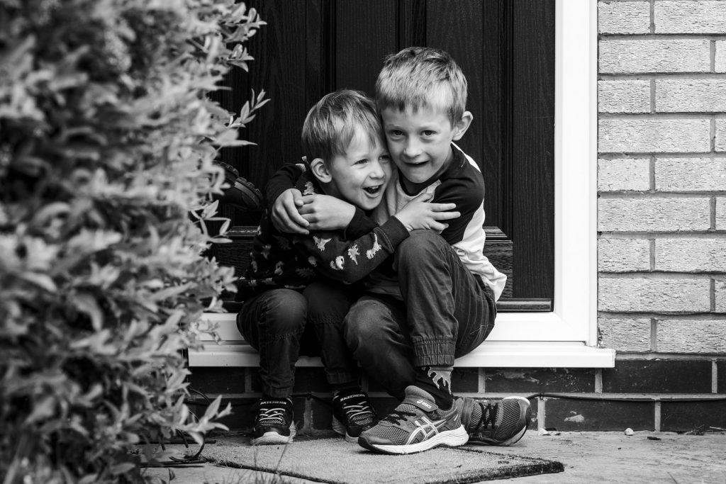 brothers cuddling on front door, doorstep portrait session