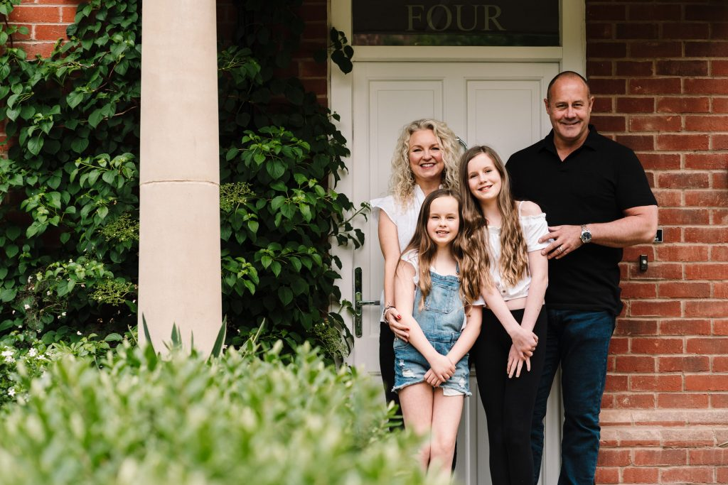 family standing together in front of their house, doorstep portrait session