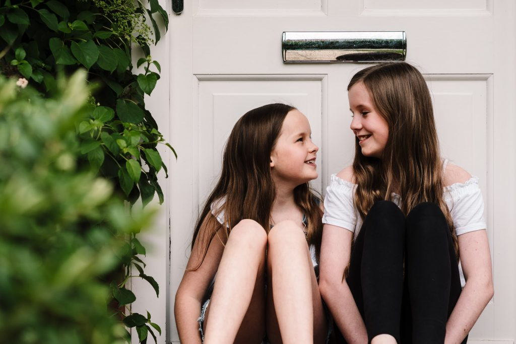 sisters sitting on front door step, doorstep portrait session