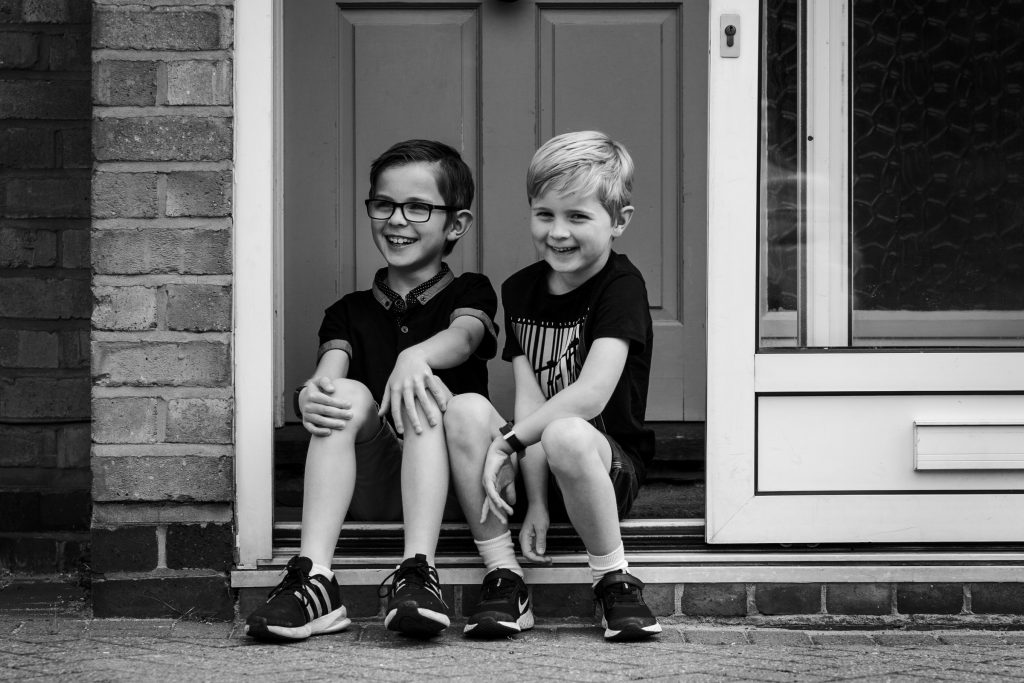 brothers sitting on doorstep laughing