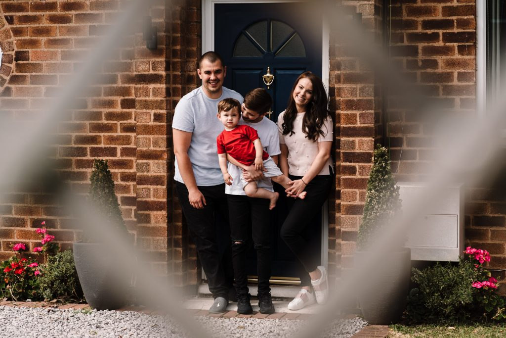 family standing on doorstep for family photo session