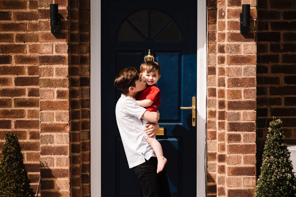 big brother cuddling little brother on front door step, family photo shoot on doorstep
