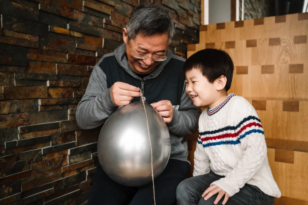 Grandad and grandson playing with a balloon