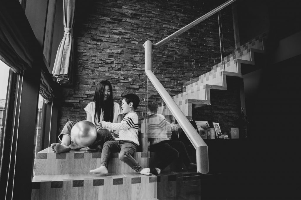 Mum and son sitting on the stairs at home during family shoot