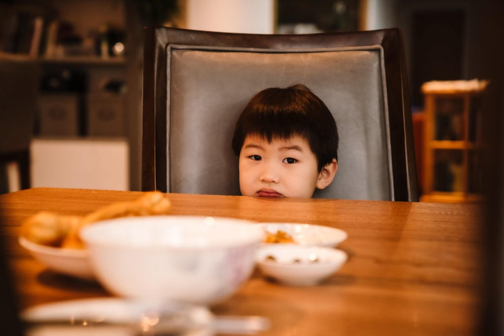 little boy sitting at the dinner table during a family shoot