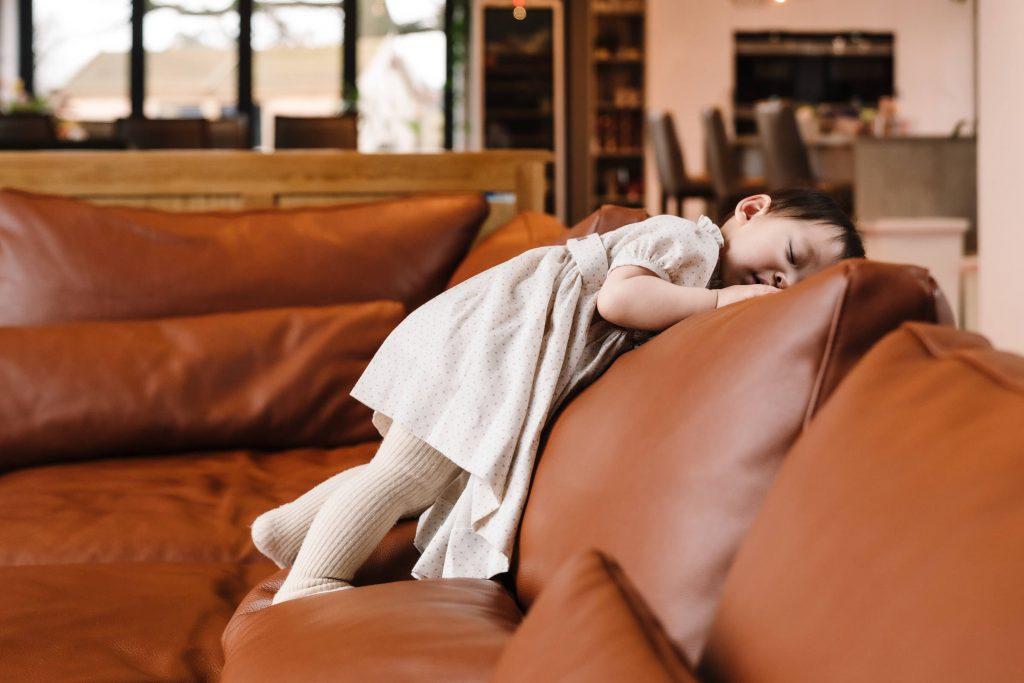 1 year old leaning on sofa, feeling sleepy