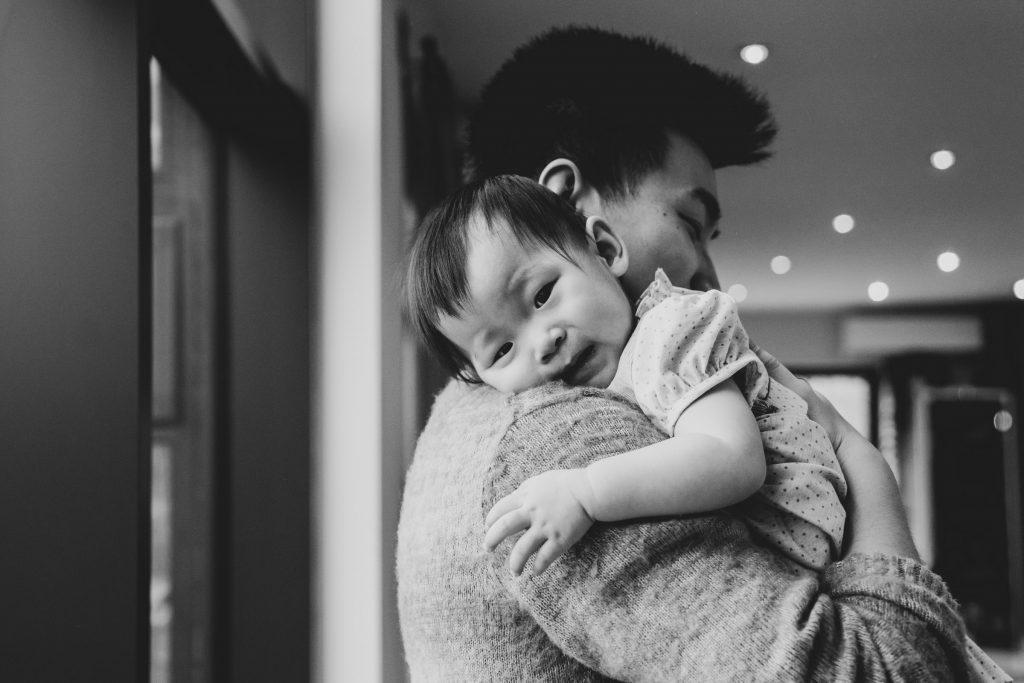 black & white image of Dad cuddling baby girl