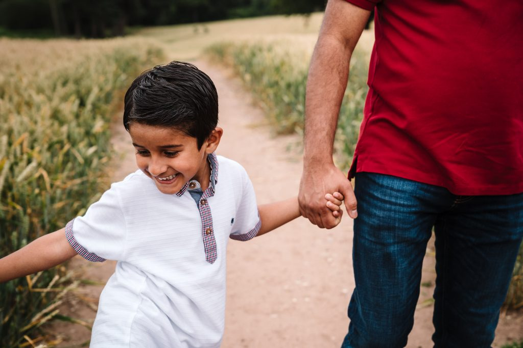 son holding hands with Dad, outdoor family photography