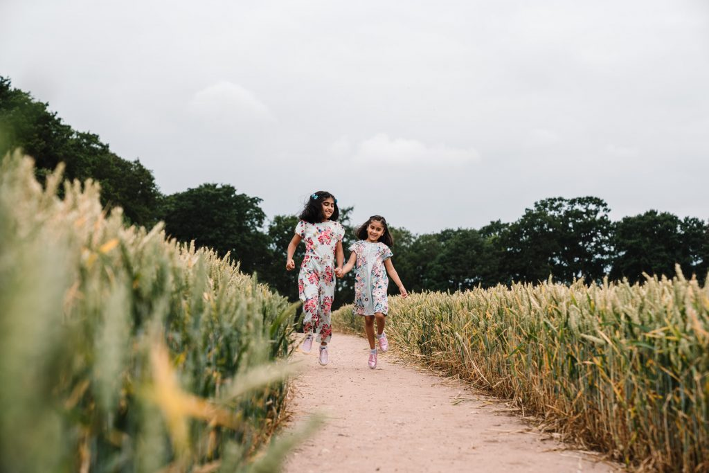 girls skipping through a field, outdoor family photography