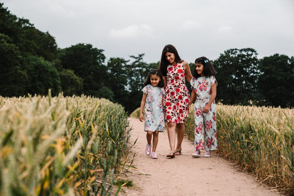 Mum and daughters walking down field, outdoor family photography