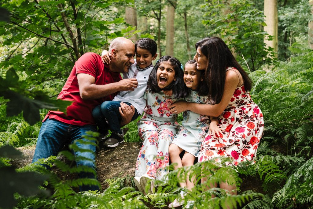 Family sitting on a log, cuddling and ;laughing during outdoor family photo shoot