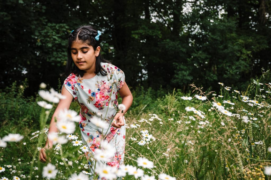 girl picking wild flowers during family photo shoot