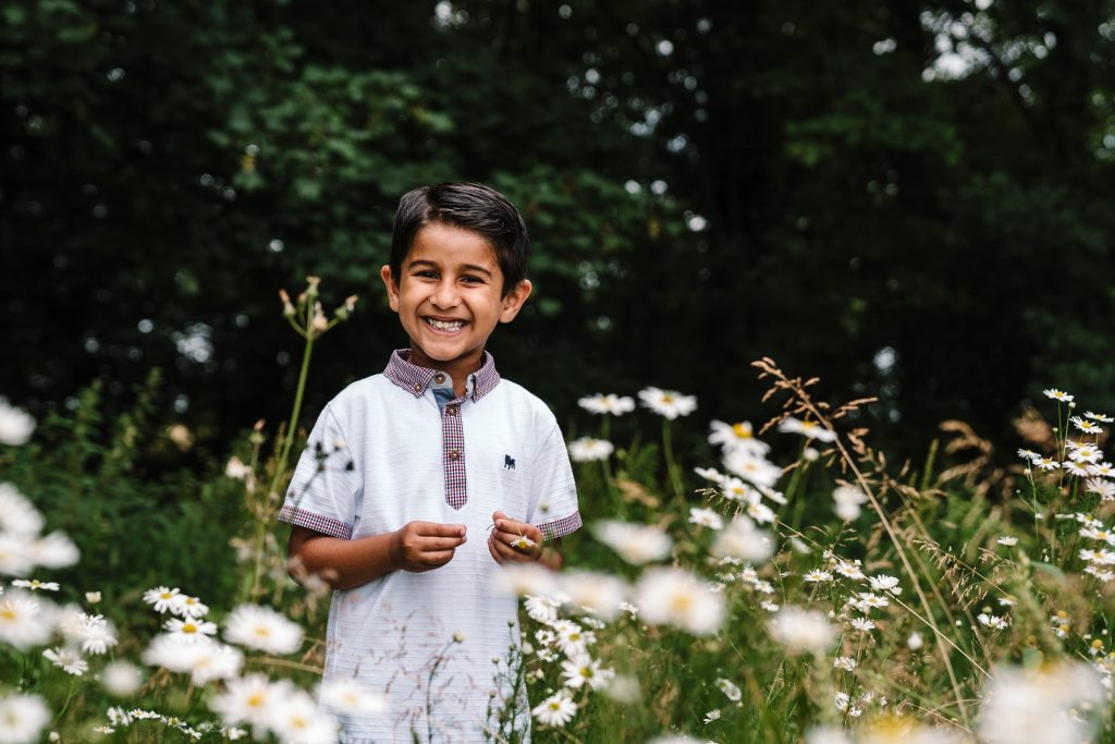 boy smiling through flowers, outdoor family photography