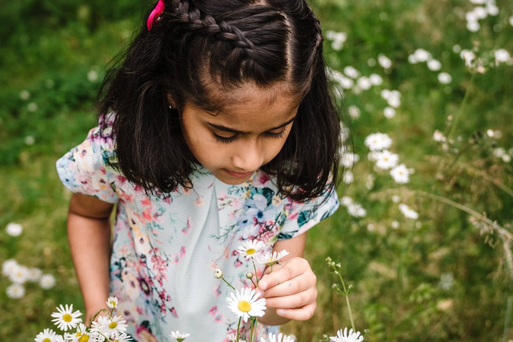 girl smelling flowers during outdoor photo shoot