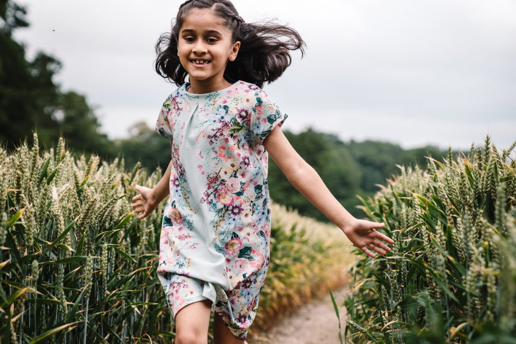 girl running through a field of wheat, outdoor photography, solihull