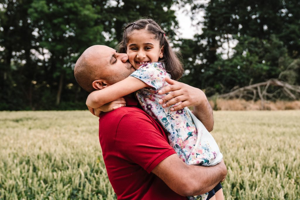 Dad kissing daughter, cuddling in a field on photoshoot