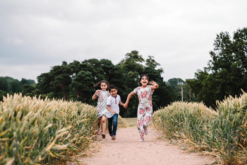 sisters and their brother running through a wjeat field during photo shoot in Solihull