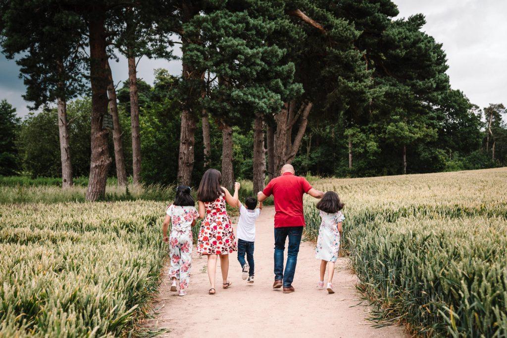 Family walking, swinging smallest child on family photoshoot
