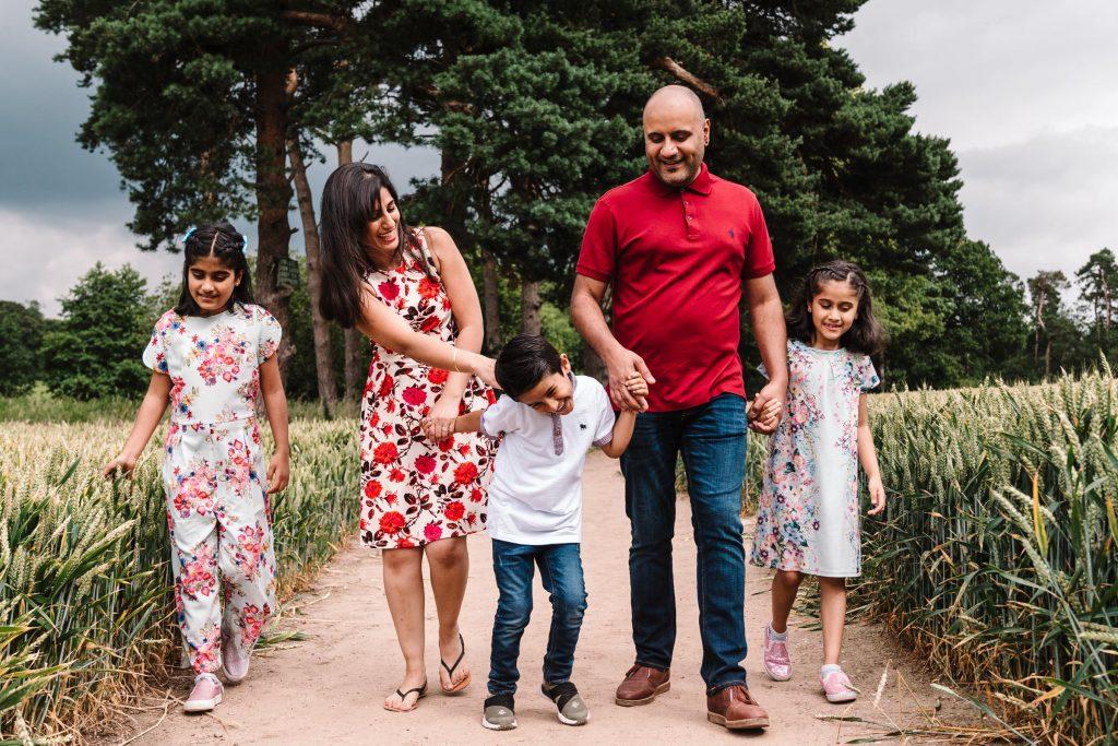 family walking through fields laughing
