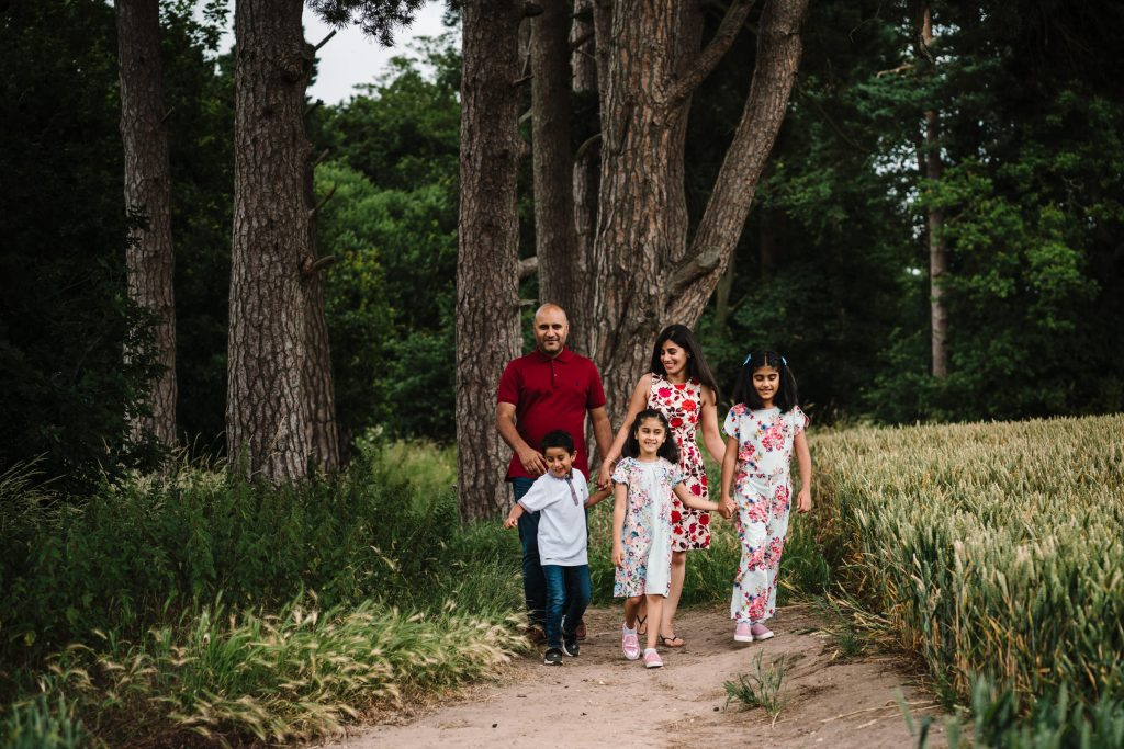 family walking through field on outdoor family shoot