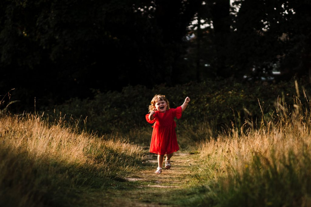 Little girl in a red dress, running and laughing through a field