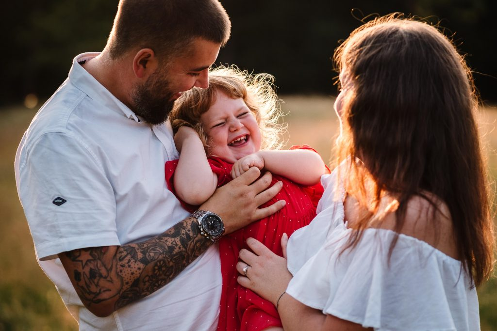Family standing together at sunset, dad tickling little girl