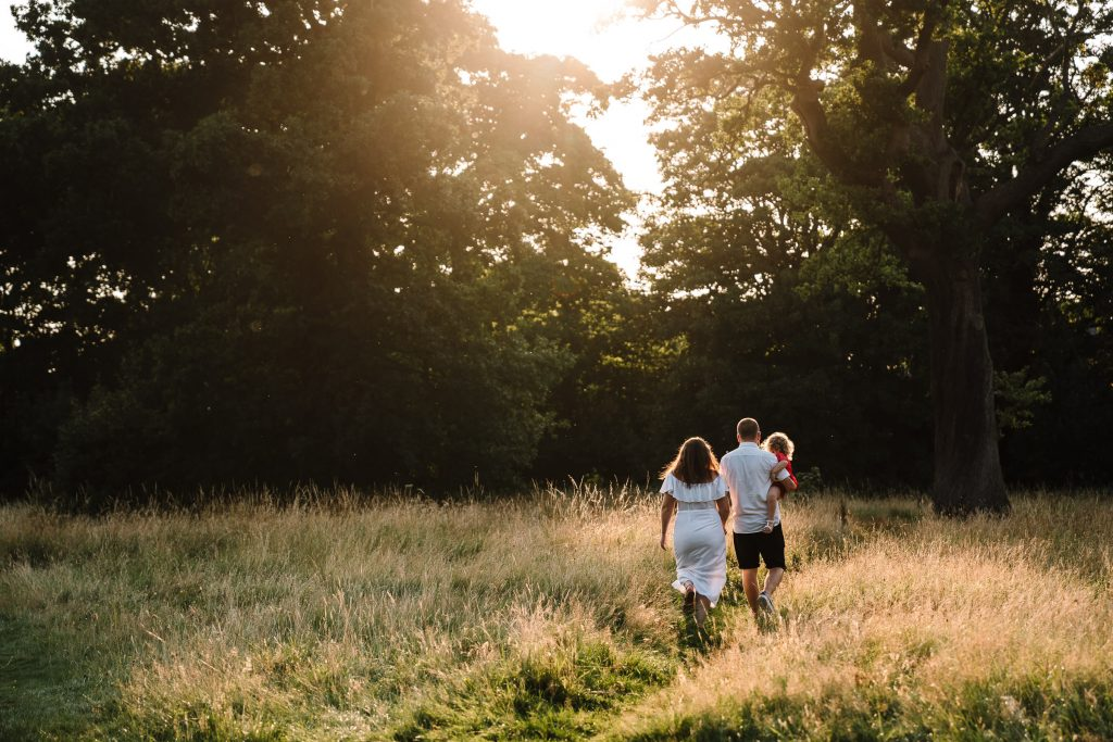 Mum, dad and little girl walking through a field of long grass at sunset