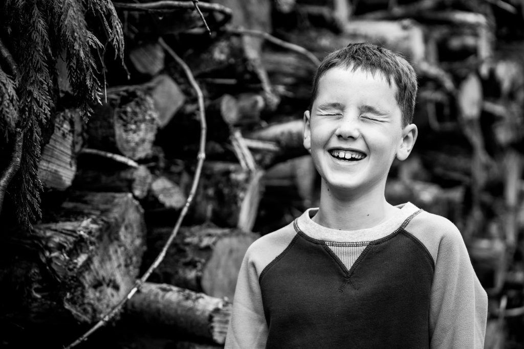 Boy laughing standing by logs